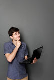 Young man with laptop looking up to copy space Royalty Free Stock Image