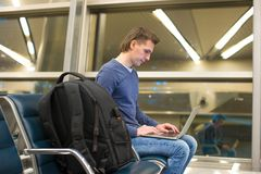 Young man with laptop and luggage at airport Royalty Free Stock Image