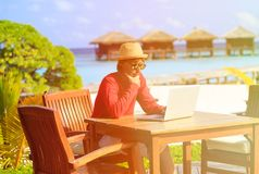 Young man with laptop at luxury beach resort Stock Photo
