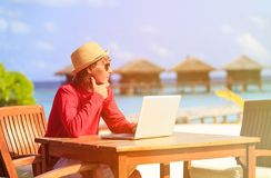 Young man with laptop at luxury beach resort Royalty Free Stock Photos
