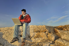 Young man with laptop outdoor Stock Photography