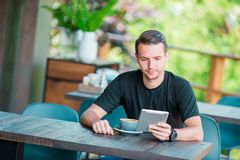 Young man with laptop in outdoor cafe drinking coffee. Man using mobile smartphone. Young man with cellphone outdoors in outdoor cafe. Man using mobile Stock Images