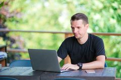 Young man with laptop in outdoor cafe drinking coffee. Man using mobile smartphone Stock Photography