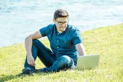 Young man with laptop outdoor sitting on the grass Royalty Free Stock Photography