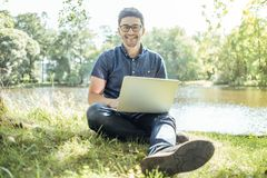 Young man with laptop outdoor sitting on the grass Stock Photos