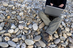 Young man with laptop outdoors. Young casual man with laptop working outdoors royalty free stock images