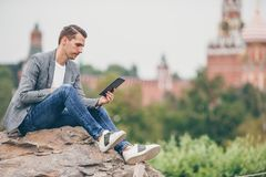 Happy young urban man in european city. Young man with laptop outdoors on background of St Basils Church and Kremlin. Portrait of businessman in Moscow stock photos