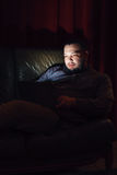 Young man with laptop rest on couch in dark room royalty free stock photo