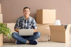 Young man with laptop sitting on carpet near boxes indoors. Moving into new house stock image