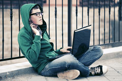 Young man with laptop sitting on sidewalk Stock Images