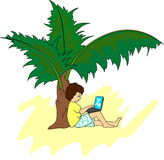 Young man with a laptop sitting on a tropical island under a pal Royalty Free Stock Photos