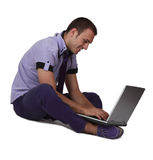 Young Man on a Laptop. Young man sitting and working on his laptop on the feet, isolated against a white background Stock Photo