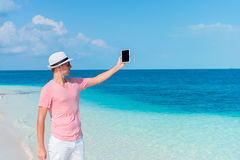 Young man with laptop on the tropical beach Stock Photography