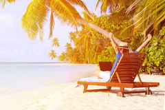 Young man with laptop on tropical beach Royalty Free Stock Images