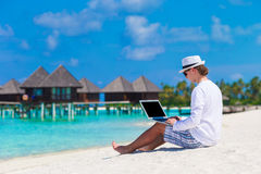 Young man with laptop at tropical beach near water Stock Image