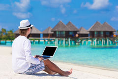 Young man with laptop at tropical beach near water Royalty Free Stock Images