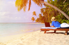 Young man with laptop on tropical beach Royalty Free Stock Image