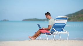 Young man with laptop on tropical caribbean beach. Man sitting on the sunbed with computer and working on the beach. Young man with tablet computer during stock footage