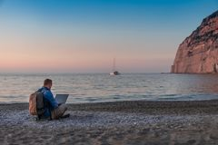 Young man with laptop working on the beach. Freedom, remote work, freelancer, technology, internet, travel and vacation concepts stock image