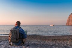 Young man with laptop working on the beach. Freedom, remote work, freelancer, technology, internet, travel and vacation concepts royalty free stock images