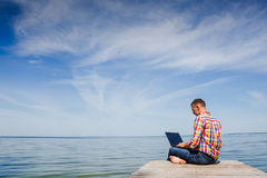 Young man with laptop working outdoor Stock Images