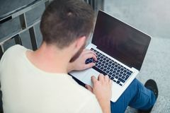 Young man with laptop working outdoors in the city Royalty Free Stock Photo