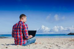 Young man with laptop working on the sand beach stock photos