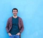 Young man laughing against blue background Stock Images