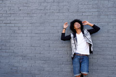Young man laughing against gray wall Stock Images