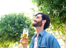Young man laughing with a beer at an outdoor bar in summer Royalty Free Stock Image