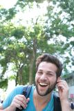 Young man laughing with earphones outdoors Royalty Free Stock Photo