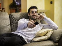 Young man laughing at funny TV show stock images