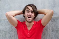 Young man laughing with hand in hair Stock Image