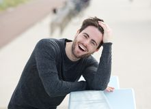 Young man laughing with hand in hair Stock Photography