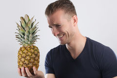 Young man laughing holding a pineapple Royalty Free Stock Photos