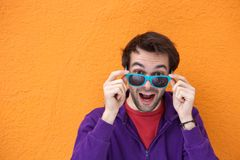 Young man laughing and holding sunglasses Royalty Free Stock Photo