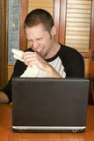 Young man laughing hysterically. At computer screen Royalty Free Stock Image