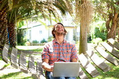 Young man laughing with laptop outdoors Royalty Free Stock Photo