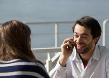 Young man laughing on mobile phone while on a date Stock Images