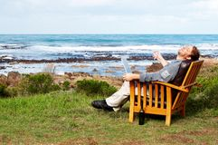 Young man laughing outdoors. Young businessman laughing at a joke on his laptop. He is sitting outside by the ocean Stock Image