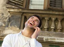 Young man laughing outdoors with mobile phone Royalty Free Stock Images