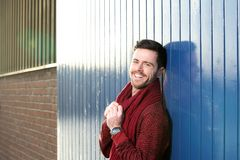 Young man laughing outdoors with sweater and scarf Stock Photography