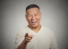 Young man, laughing, pointing with finger at someone Royalty Free Stock Photography