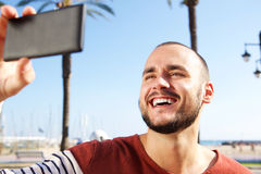 Young man laughing when taking a selfie with mobile phone Royalty Free Stock Images