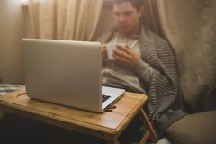 Young man laying in bad with laptop and cup of tea. Stock Image
