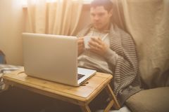 Young man laying in bad with laptop and cup of tea. Royalty Free Stock Photo