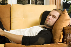 Young man laying on couch. In living room Stock Image