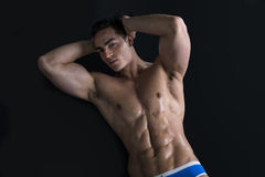 Young man laying on the floor with naked muscular body Stock Images