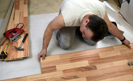 Young man laying the floor panels Royalty Free Stock Image