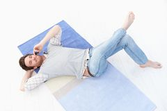 Young man laying on floor using mobile smiling Stock Photos